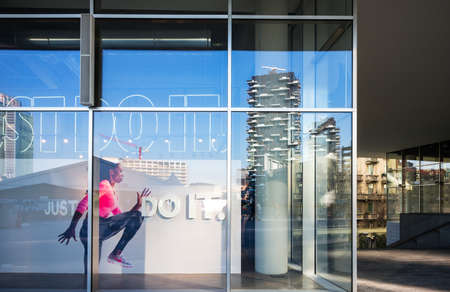 Milan, Italy - February 10, 2015: Porta Nuova, reflections on a shop window of Aulenti square