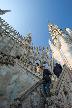 Milan, Italy - April 21, 2011: People between the spires and marle works of the Duomo cathedral rooftop Stock Photo - 56983639