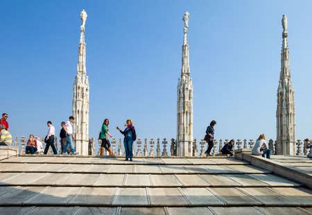 Milan, Italy - April 21, 2011: People between the spires and marle works of the Duomo cathedral rooftop