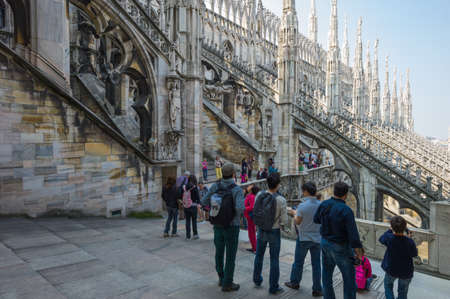 spires: Milan, Italy - April 21, 2011: People between the spires and marle works of the Duomo cathedral rooftop