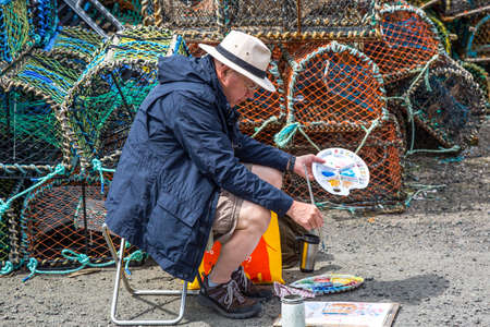 fife: Crail, Scotland - July 26, 2012:  Fife area, a painter in the harbor.