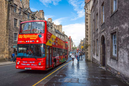 mile: Edinburgh, Scotland - July 28, 2012: A tour bus in the Royal Mile looking towards Holyrood.
