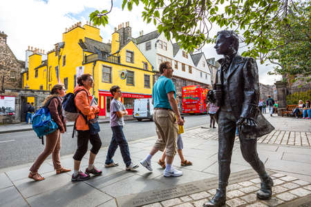 mile: Edinburgh, Scotland - July 28, 2012: Royal Mile, Canongate, tourist walking near the statue of the poet Robert Fergussont. Editorial