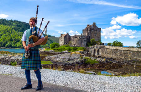 bagpipe: Lochash,  Scotland -  June 20, 2012: Highlands, a bagpipe player and the Eilean Conan castle in background. Editorial