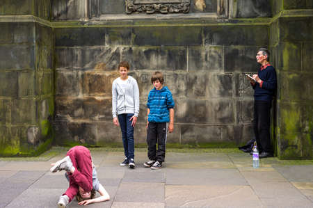 giles: Edinburgh,  Scotland -  July 24, 2012:  Royal Mile, boys playing alongside the St Giles Cathedral.