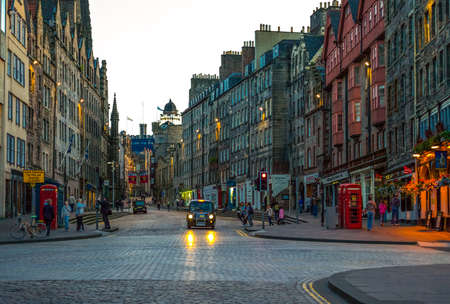 obscura: Edinburgh, Scotland - July 25, 2012: The Royal Mile looking towards the Castle, with the Camera Obscura tower in the background, at sunset.