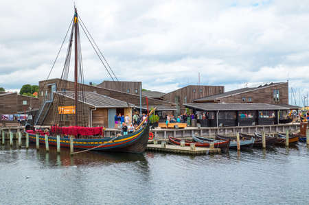 Roskilde, Denmark - July 23, 2015: Replicas of ancient boats and visitors outside the Viking Ship Museum