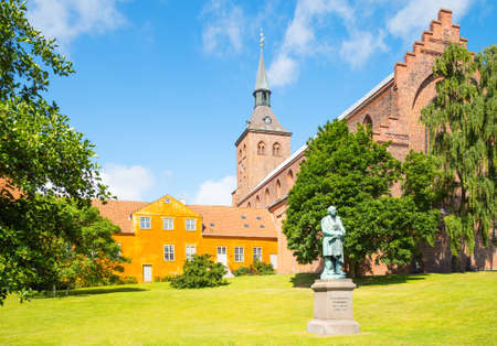 Odense, the gothic St. Canutes Cathedral with the Hans Christian Andersen monument in the foreground Stock Photo