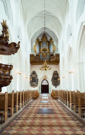 nave: Odense, Denmark - July 21, 2015: The nave of the gothic St. Canutes Cathedral with the ancient organ