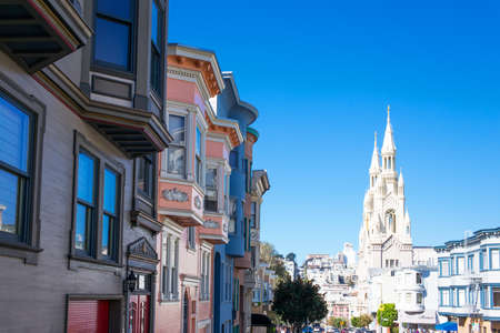 San Francisco, USA - September 23, 2015: The traditional colored houses of Filbert street with the St Peter and Paul church in the background.