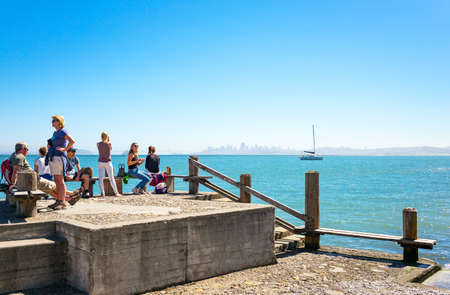 Sausalito, USA - September 23, 2015: Tourists on a pier looking at the bay with the San Francisco skyline in the background