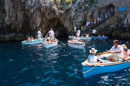 Capri, Italy - August 5, 2015: Boats with tourists waiting to get into the Blue Grotto