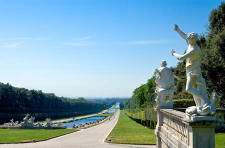Italy, Caserta, panoramic view of the park of the Royal Palace with marblr statue in the foreground Stock Photo