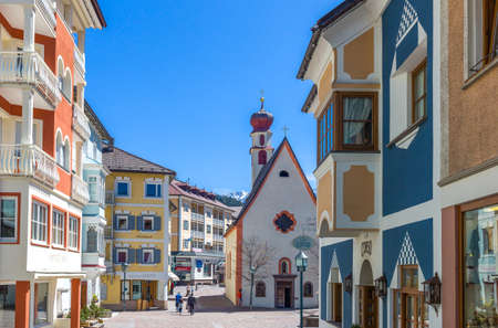 Ortisei, Italy - April 28, 2012: Yhe houses and the parish church of the historic town center