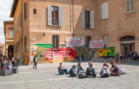 Bologna, Italy - May 5, 2016: University district, students sitting in Giuseppe Verdi square