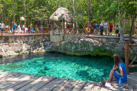 Coba , Mexico - April 20, 2016: Tourists bathing in the sinkhole of the archaeological site