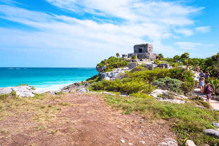 Tulum, Mexico - April 20, 2016:  Sea view from the Mayan city archaeological site, with tourists on the right