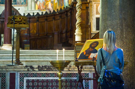 Rome, Italy - September 29, 2008:  A young woman in the interior of S.Maria in Trastevere
