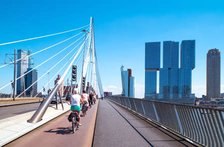 Rotterdam, The Nederlands - July 18, 2016:  Cyclists crossing the Erasmus bridge on the Maas river with the De Rotterdam towers in the background