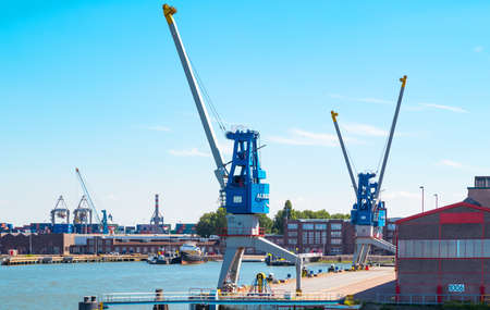 Rotterdam, The Nederlands - July 18, 2016: Goods handling equipment and cargo ships in the main commercial harbor of the city Redactioneel
