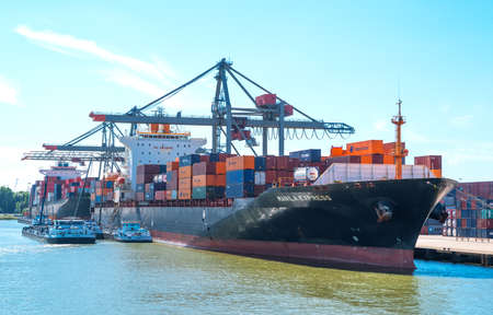 Rotterdam, Nederland - 18 juli 2016: Goederenbehandelingsapparatuur en vrachtschepen in de belangrijkste commerciële haven van de stad