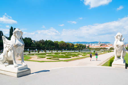 Vienna, Austria - August 7, 2016:  The garden with Sphinx statues of the Belvadere Palace with the lower palace in the background