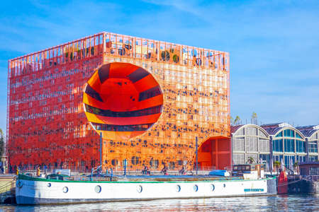 Lyon,  France - December 9, 2016: Confluence district, the Orange Cube building on the Saone river bank