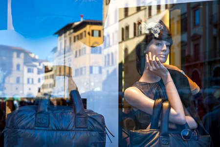 Florence, Italy - October 13, 2009:  The palaces of Della Signoria square reflected on a shop-window
