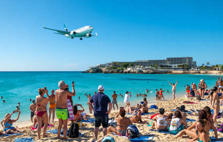 Philipsburg, St Maarten - January 27, 2019: A commercial jet approaches Princess Juliana airport above onlooking spectators on Maho beach Editorial