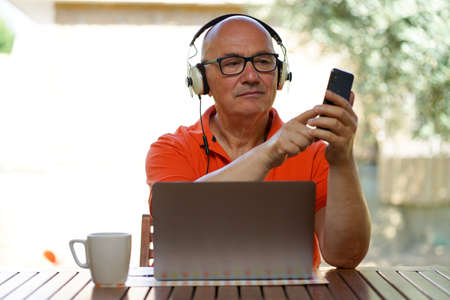 Senior caucasian male with glasses is working at home with laptop, smartphone and headphone. A cup of coffee. Stock fotó - 153225067