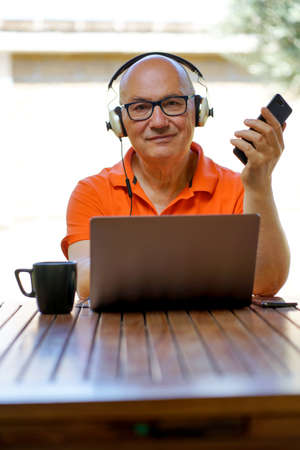 Senior caucasian male with glasses is working at home with laptop, smartphone and headphone. A cup of coffee.
