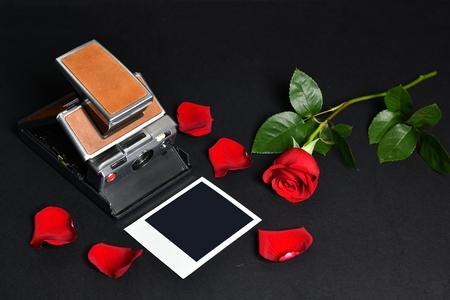 Vintage camera and red rose with petals on a black background gift of love Reklamní fotografie