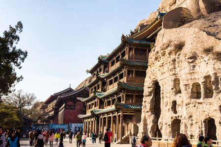2014 년 11 월 - 대동 (Datong), 중국 - 가장 아름답게 세공 된 중국 불상을 전시하여 대동에서 용강 석굴을 탐험하는 관광객