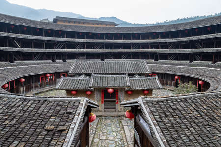 Feb 2015 - Fujian province, China - Jiqing Lou in ChuXi Cluster. The tulou (tu = earths, lou = building) are ancient earth dwellings of the Hakka people, still inhabited by local communities. Here in the middle the family temple of the village. Banco de Imagens