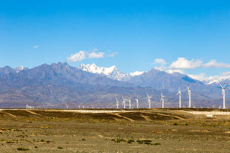 Aug 2017 – Xinjiang, China – A Wind farm near Urumqi, with the majestic height of Tianshan behind it. The deserts of Xinjiang, the westernmost province of China, are full of Wind Turbine Power Plants Archivio Fotografico