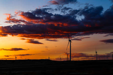 Aug 2017 – Xinjiang, China – Wind Turbines at sunset in Burqin County, North of Xinjiang. The deserts of Xinjiang, the westernmost province of China, are full of Wind Turbine Power Plants Archivio Fotografico