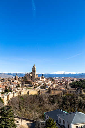 Segovia, Spain? View from Juan II tower in Winter time of the Alcazar of the old town of Segovia and the Cathedral with the snow capped Sierra de Guadarrama behind