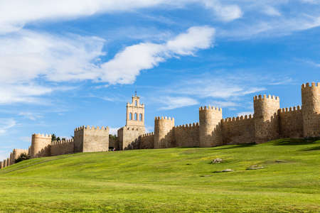 View of the medieval city walls from the city of Avila, Spain, and the green lawn in front of the Puerta del Carmen. Called the Town of Stones and Saints