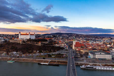 Bratysława, Słowacja: widok z lotu ptaka na stare centrum miasta o zachodzie słońca po drugiej stronie Dunaju