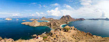 Tourists observing the panoramic view from the top of Padar Island in Komodo National park in autumn, Lubuan Bajo, Flores, Nusa Tenggara, Indonesia