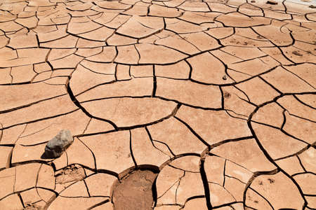 Cracked clay soil in front of the Flaming Mountains in China, Xinjiang province. Located in the Turpan depression, this site is extremely dry and hot in summer Imagens