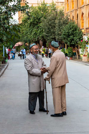 Aug 2017, Kashgar, Xinjiang, China: two local men warmly shaking hands in the streets of Kashgar Old Town, a major tourist spot along the Silk Road and one of the westernmost cities of China