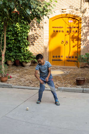 Aug 2017, Kashgar, Xinjiang, China: local Uighur child playing spinning in the streets of Kashgar Old Town, a major tourist spot along the Silk Road and one of the westernmost cities of China