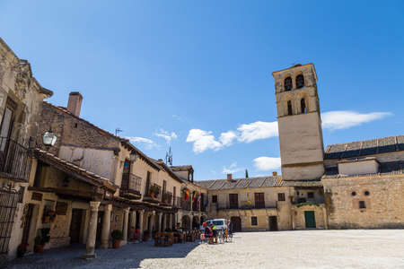 May 2019, Pedraza, Castilla Y Leon, Spain: tourists near Iglesia San Juan Bautista in the Plaza Mayor. Pedraza is one of the best preserved medieval villages of Spain, not far from Segovia