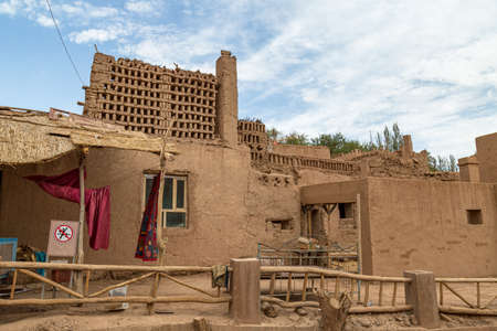 Aug 2017 Tuyoq village (Tuyuk): one of the streets of this traditional Uighur village sets a lush valley cutting through the flaming mountains near Turpan, Xinjiang, China Imagens - 127627411