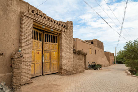 Aug 2017 Tuyoq village (Tuyuk): one of the streets of this traditional Uighur village sets a lush valley cutting through the flaming mountains near Turpan, Xinjiang, China Imagens - 127627413