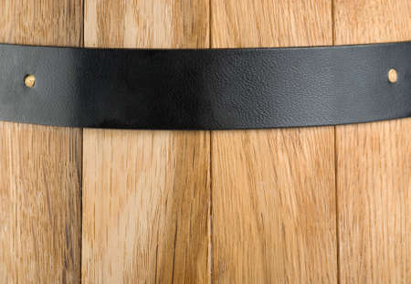 Background of a wooden barrel and a metal strip