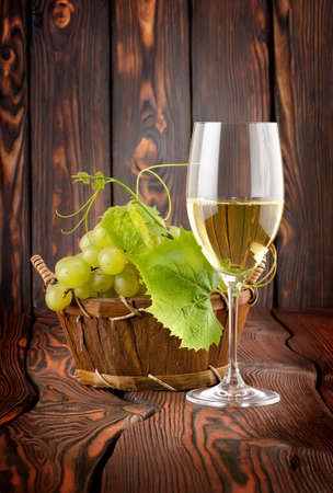 Glass of white wine and grapes photo