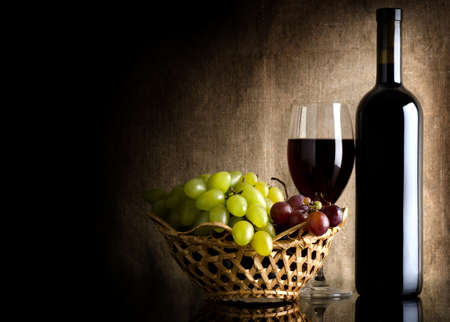 Bottle of red wine and grapes on a background canvas photo