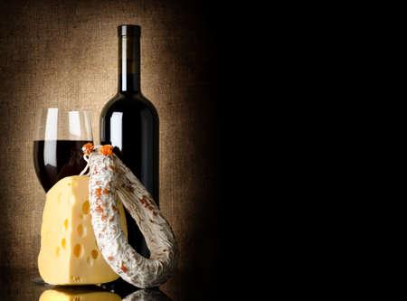 vinos y quesos: Vino, queso y salami sobre un fondo de tela vieja